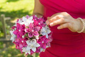 Für die Zeremonie: ein Brautstrauß aus rosafarben und weißen Papierblüten mit Perlen.